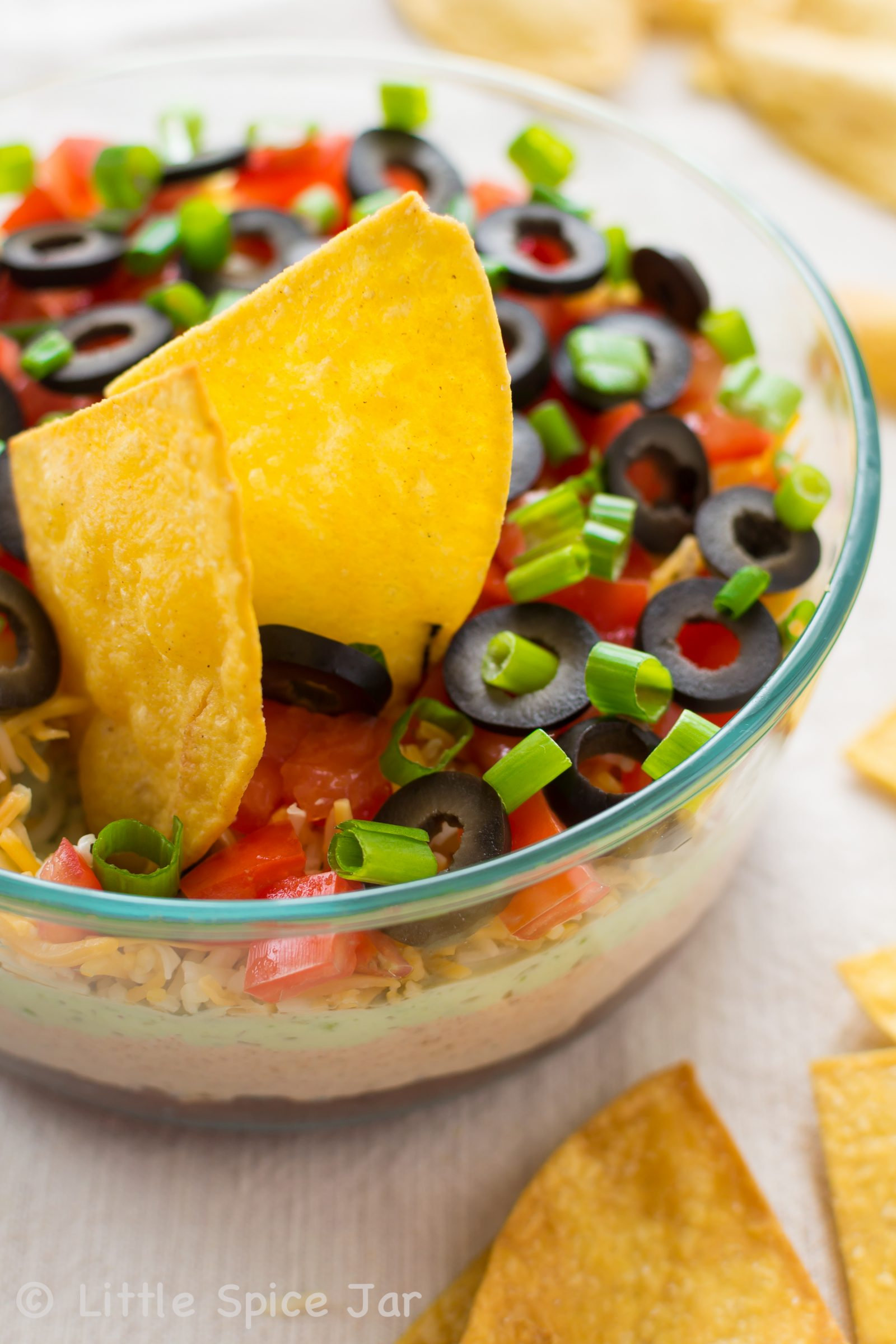 SKINNY SEVEN LAYER DIP WITH HOMEMADE TORTILLA CHIPS - Little Spice Jar